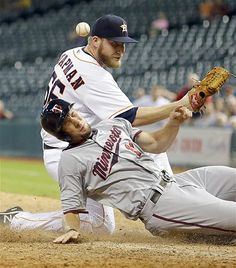Minnesota Twins' Clete Thomas slides across home plate to score on a wild pitch as Houston Astros relief pitcher Kevin Chapman loses the bal...