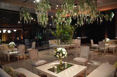 Cocktail en recepcioón vidriada: livings compuestos de 2 sillones cada uno, y 2 sillas de estilo Luis XV blancas, centros de mesa en copones verdes con flores blancas y tapa de espejo, y glicinas y bombitas de luz dimerizadas colgando desde el techo. En el centro, una mesa con diferentes plantas y follaje, By Mercedes Courreges Ambientaciones