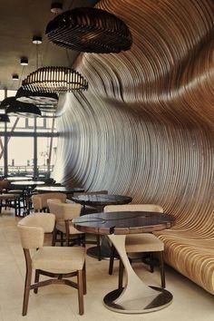 Don Café House . Los colores marrones y las formas redondeadas alusivas a los granos de café en lámparas y mesas.  Destaca la suavidad de las curvas de la madera que recubre las paredes y da consistencia a los bancos integrados en ella.  #Esmadeco.