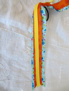 Flower Frenzy Pony-O with brightly coloured grosgrain ribbon attached to a pony tail holder, easily make a dressed up pony tail or bun. www.intheloopgear.ca