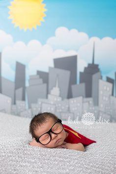 Newborn boy in Superman cape in front of city skyline backdrop. Superman newborn session by Pueblo newborn photographer K.D. Elise Photography.