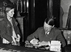 """One of Hitler's favorite activities was interacting with children, """"the future of the """"Reich."""" Here, he signs the autograph book of one young admirer."""