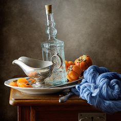 Still life with persimmons, blue bottle and light blue drapery on wooden table in kitchen.