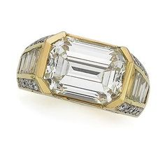 Gold and Diamond Ring, Cartier Centering one cut-corner emerald-cut diamond approximately 7.00 cts., within a polished gold border, flanked by 8 baguette diamonds, accented by 50 round diamonds, altogether approximately 2.25 cts., signed Monture Cartier, approximately 6.8 dwt.