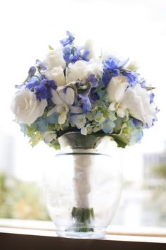 Bridesmaids would carry these beautiful nosegay bouquets of white roses, bi-color hydrangea, white orchids, and blue larkspur