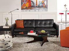White walls, colorful accents, dark leather sofa, wood table, colored side chair
