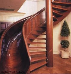 Here's the staircase slide in the home of Scott Jones, an old country manor he converted into a high-tech home with all the fixings... including a mahogany corkscrew slide with fibre optic lighting running down the side. The slide was designed and built by local wood craftsman, Rodney Miller, from Anderson, Indiana, and took 15 months to complete. Scott had asked for a fast slide, and Rodney delivered. The 17' tall slide with a 13' drop is both fast and beautifully suited for the regal home.