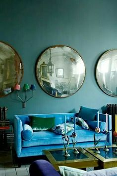 giant round mirrors, bright turquoise blue sofa, amazing teal walls