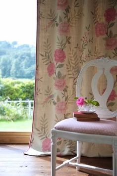 Sarah Hardaker - Chinoiserie Fabric Collection - Carved white chair with a light pink fabric seat, in front of floor-length floral curtains in cream, with a green and rose pink pattern