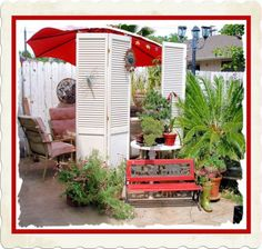 Old Shutters- I created a side yard area  using shutter doors as privacy dividers and added plants hubby added feet so they didn't blow over in the wind.  Child's bench was  found thrown away along side the road by hubby he fixed and painted it.