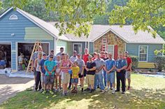 Volunteers from the police academy work to repair a local home