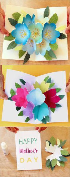 ein tisch aus holz und pop up karten mit gefalteten blauen, violetten, roten und gelben blumen aus papier, basteln zum muttertag, blumen mit vielen grünen blättern aus papier