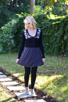 Grey skirt, argyle sweater, grey ankle boots, blonde curly hair