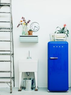 LOVE everything about this. white walls, ladder, blue fridge, flowers, clock, pastels + bold color on white mixed with industrial!