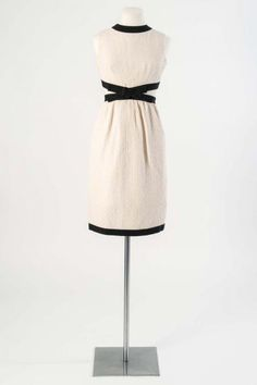 Yves Saint Laurent, c.1965.  White silk crepe cocktail dress with cut-away bodice, trimmed with black Petersham ribbon and bows. Worn by prima ballerina Dame Margot Fonteyn.