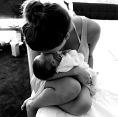 Love this picture of mommy and her new Born sitting on the bed in a casual outfit!