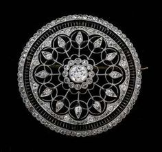 A fine Edwardian diamond pierced openwork circular brooch   centred with an old European cut and a border of rose-cut diamonds, fine metal work surround with diamonds set throughout. In a miligrain setting. Tested as platinum. Centre diamond weighing