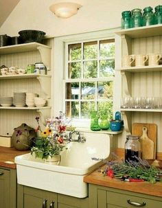 Great Farm sink in this kitchen with painted green cabinets and open shelving with bead board behind it. Farm kitchen