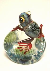 """Jeremy Sinkus's Frog Paperweight.  Red legged with bulging eyes, sitting atop an underwater seascape. Encased in clear glass, artist signed J Sinkus and approximately 2.40"""" w x 3.0""""h x 1.55""""d."""