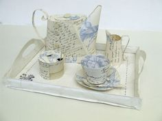 Decorative Paper Tea Set, of a teapot, milk jug, sugar bowl (with spoon), teacup with saucer (and spoon), and presented on an embroidered paper tray. The work has been created from wallpaper and vintage letters. It is made by manipulating and stitching the found papers to create the forms.