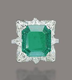 AN EMERALD AND DIAMOND RING, BY MOUAWAD   Set with an octagonal-cut emerald, weighing approximately 5.80 carats, to the pear-shaped diamond surround, mounted in platinum, ring size 5¼ with ring sizer  Signed Mouawad