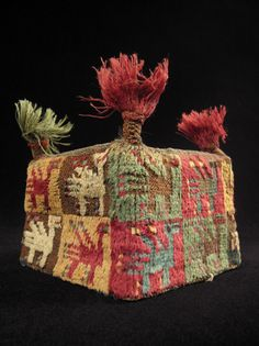 """four-cornered hat from the Huari culture of the Highlands of Peru. Made of camelid wool yarns and natural dyes, it has a mesh screen on the top to contain the fragile wool and is mounted over a cardboard form. It measures 5"""" square and stands 3.5"""" high.  A.D. 700-1000."""