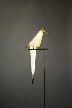 """Umut Yamac - Perch Light - """"The Perch Light is a balancing sculptural light made of folded paper and brass. The lamp takes the form of an abstract bird which appears to be delicately balanced on its metal perch. The bird is illuminated through contact with the perch and this lets the bird balance and swing without any cables whilst maintaining luminance"""""""