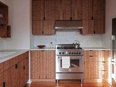Lovely cabinetry. Cabinets above hood, and surrounding it.  Stainless fridge and range.  Under-mounted sink, marble top.