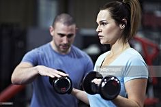 Healthy female lifting dumbbell free weights in gym with encouragement from personal trainer
