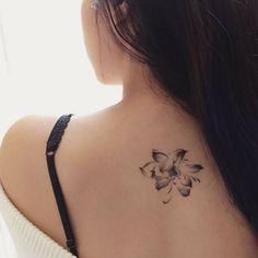Tatuaje de una flor de loto en la parte alta de la espalda de...