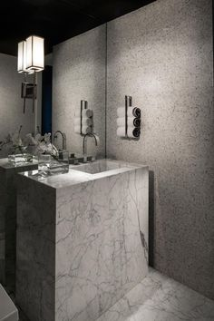 The bathroom branches out with a striking marble vanity paired with a floor-to-ceiling mirror and mosaic tile walls.