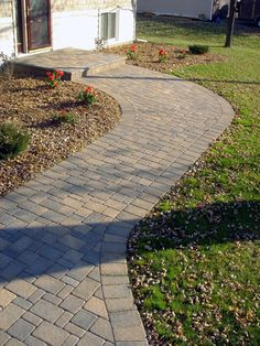 A simple Cobblestone walkway breaks up the monotony of this yard.