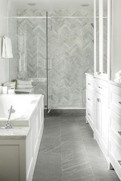 Carrera marble herringbone wall tile, Carrera tile, grey porcelain floor tile, white cabinetry, glass shower wall and door, chrome fixtures, soaker tub