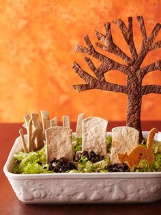 Tombstone Taco Dip...  ingredients  1  16-ounce can refried beans with green chiles  1/4  cup bottled salsa  2/3  cup bottled ranch salad dressing  2  teaspoons taco seasoning  1 1/2  cups finely chopped cooked chicken  1  7-ounce pouch refrigerated guacamole  1/2  of a 2 1/4-ounce can chopped pitted ripe olives, drained  shredded lettuce  10-inch tortillas     directions  In a small bowl, combine refried beans and salsa. Spread refried bean mixture in a 2-quart rectangular dish. In a small bowl, combine ranch salad dressing and taco seasoning; stir in chicken.  Spoon on top of the beans in an even layer. Spoon guacamole in small mounds on top of the chicken mixture. Carefully spread to an even layer.  Cover and chill at least 30 minutes or up to 6 hours before serving. Just before serving, place tombstone characters into dip. Sprinkle the graves with chopped olives and shredded lettuce.  Serve with tortilla chips. Potluck Recipes, Appetizer Recipes, Fall Recipes, Halloween Appetizers, Halloween Food For Party, Ranch Salad Dressing, Scary Halloween, Halloween Costumes, Halloween Ideas