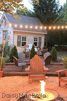 Great idea for a backyard. Pea gravel, Adirondack chairs, string of lights, and fire pit!