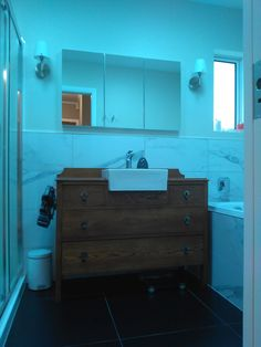Look at my bathroom vanity! I got an old 1930's / 1940's oak chest of drawers and got a cabinet maker to fit the basin. It has all been fixed up and sprayed. Doesnt it look gorgeous??! I particularly love the sconces/lights on the wall and the cararra marble tiles....