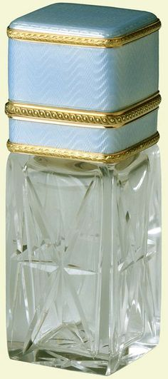 Fabergé scent bottle of rock crystal, square in section with four panels of eight-pointed stars, red gold collar and hinged lid with pale translucent blue guilloché enamel and palm leaf bands. Mark of Henrik Wigström, 1908. Bought by Lord Revelstoke; by whom given to Queen Mary, when Princess of Wales, 1909.