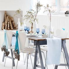 Mimic the icy colors of winter with this blue-and-white Christmas color scheme. Birch logs, frosted pinecones, and branches in white ceramic vases provide the indoor winter wonderland. Accent with blue velvet ribbon and clear blue goblets for  cool pops of color.