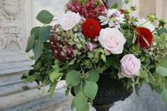 Wedding flower arrangement with red dahlias and pink roses for a romantic fall wedding in Italy.
