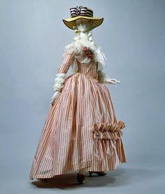 El vestido a la inglesa, muestra el gusto prerrevolucionario por la moda de este país.La chaqueta corta, con amplias solapas y manga larga, se inspiran en la indumentaria masculina.  Una bajofalda de montar, remplaza al miriñaque, y un pequeño cojín en la parte posterior acentúa esta forma, el cul de Paris, que iba prendido detrás bajo la falda. El vestido entallado construido sobre una ballena, ciñe cómodamente el cuerpo, de la cintura cae una falda mas larga por detrás formando una cola…