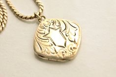 Antique Victorian or Edwardian gold-filled locket necklace. Almost-square or diamond-shaped locket has rounded corners, ornate engraved designs, and