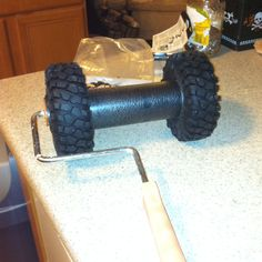 husband is a genius! I wanted to find a way to paint tire tracks on the nursery wall. That's a paint roller with huge RC truck tires on it and a scrap piece of rubber in between to keep the tires uniformly apart. I think this will work perfectly!