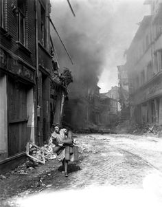 A poignant image of the feebleness of human existence in the face of the Gates of Hell: A German woman carrying her possessions runs from the burning city of Seigburg, 1945.