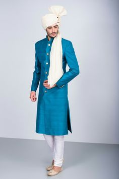 EKAKSH - blue raw silk achkan with off white chudidar and golden buttons #flyrobe #groom #groomwear #groomsherwani #sherwani #flyrobe #wedding #designersherwani
