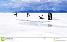Salar de Uyuni Bolivia - panorama of the perfect white flat salt desert with blue cloudy sky. Group of young people having fun posing and taking photos. Visible salt crystals hexagonal texture.  blue,bolivia,desert,flat,panorama,people,salar,salt,sky,texture,uyuni,white,young,adventure,altiplano,america,andean,andes,background,beautiful