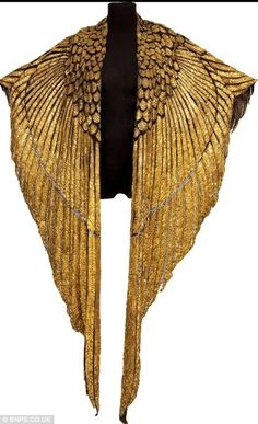 Wings of Gold -- Screen legend Elizabeth Taylor wore the golden cape in the 1963 film Cleopatra. The leather and gold garment, designed to look like the wings of a Phoenix, is intricately designed using thin strips of gold leather and embellished with thousands of seed beads, bugle beads and bead-anchored sequins. Photo of overall shape at click.