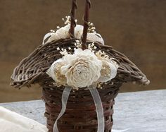 This sweet little basket is perfect for a rustic wedding. I love the details of the basket with the weaving of twine and moss. I added some preserved babys breath around the rim. This preserved babys breath is pliable and wont break off. Both sides have ivory burlap leaves, a sheer bow and an ivory sola flower. Measurements ~ 12 tall at the top of the handle, 6 x 6 and 3 1/2 - 4 deep. Please note that each basket is slightly different due to being handmade (not by me) and I decorate them as…