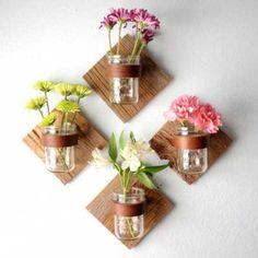 Una idea genial para esos botes de cristal que perfectamente pueden decorar una pared con aquellas flores que más te gusten y que aportan el color que más te guste