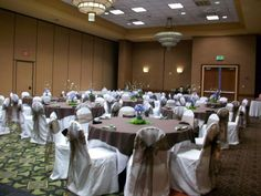 White chair covers with chocolate organza sashes and chocolate overlays on a white tablecloth