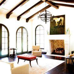 beams. arched windows. art. herringbone brick in fireplace.